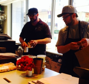 L-R: Brick 29 and On the Fly owner and chef Dustan Bristol and manager Doug Stinson cranking out sandwiches, soups, salads and desserts for the lunch hour crowd. Photo by Jeanne Huff